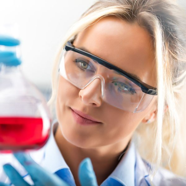 Happy young attractive female scientist with protective eyeglasses and gloves holding a flask with red liquid substance in the chemical research laboratory